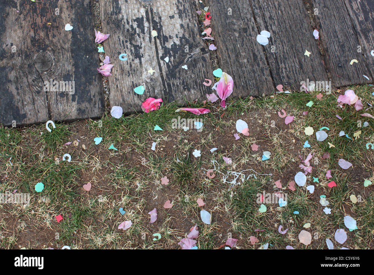 Confetti at a summer wedding, fallen on textured wood and green grass - Stock Image