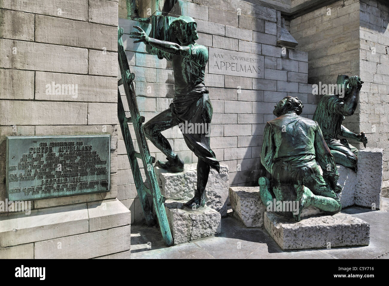 Sculpture group showing medieval labourers and stone carvers in front of the Cathedral of Our Lady in Antwerp city, - Stock Image