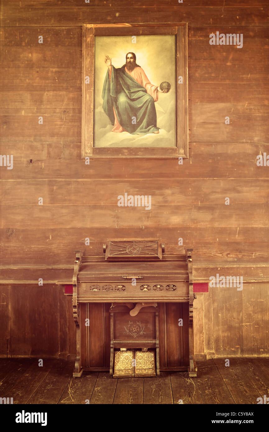 An antique pump organ stand below a painting of God in the Cataldo Mission, Idaho. - Stock Image