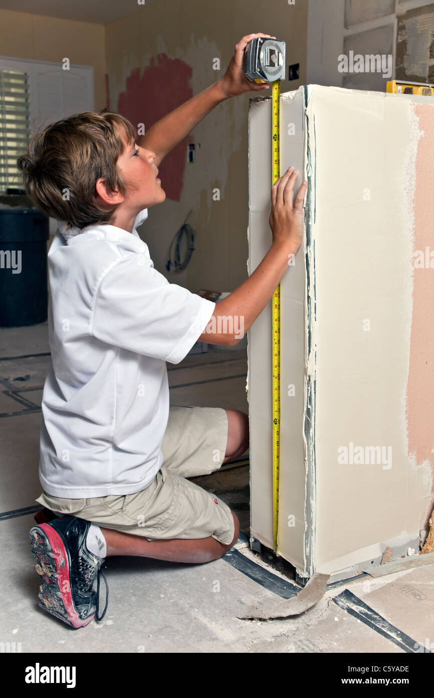 11-12 year years old caucasian boy measures pony wall during kitchen remodel. MR © Myrleen Pearson - Stock Image