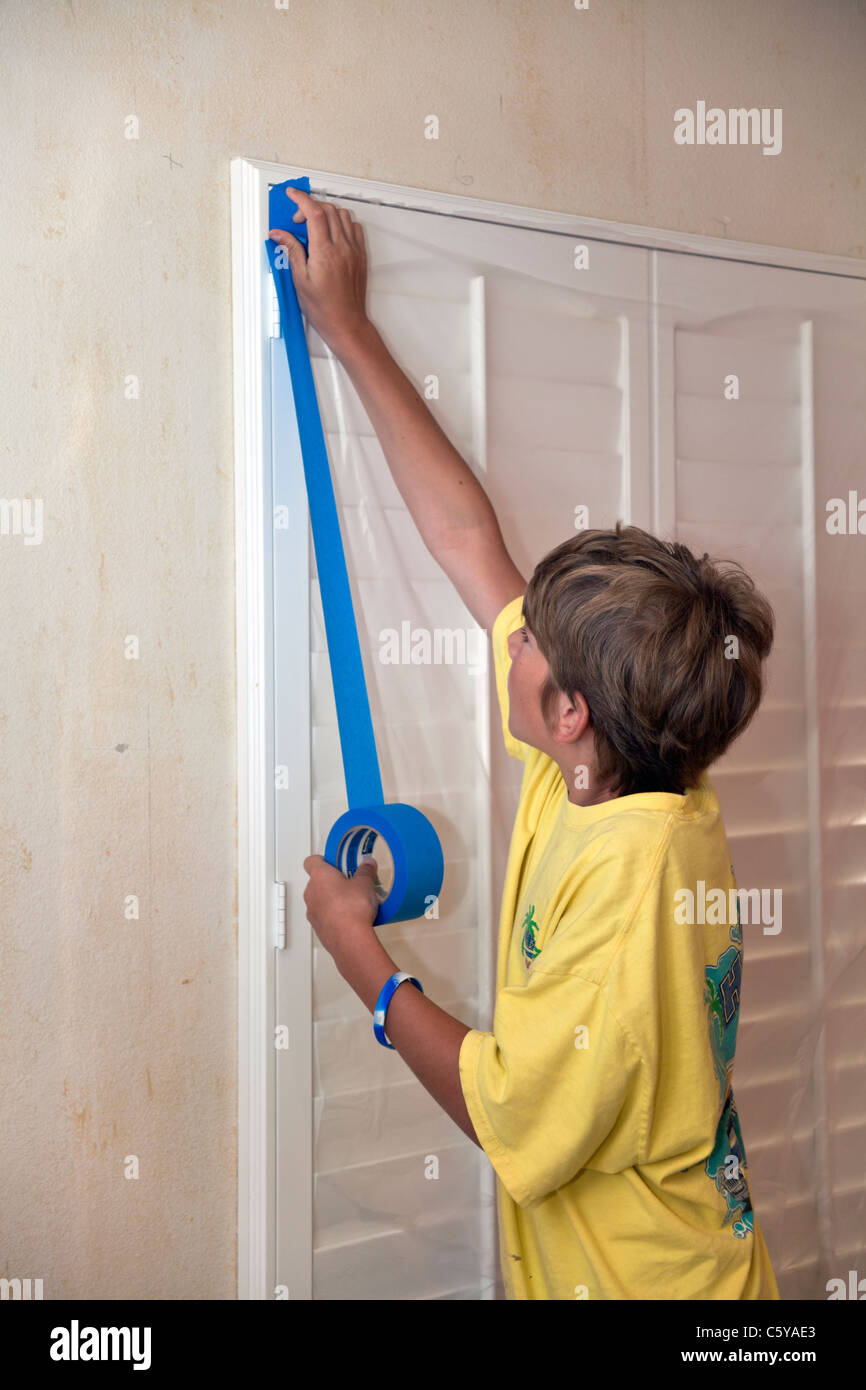 11-12  year years old caucasian boy helping dad father take child to work daywork applying painter's tape to - Stock Image