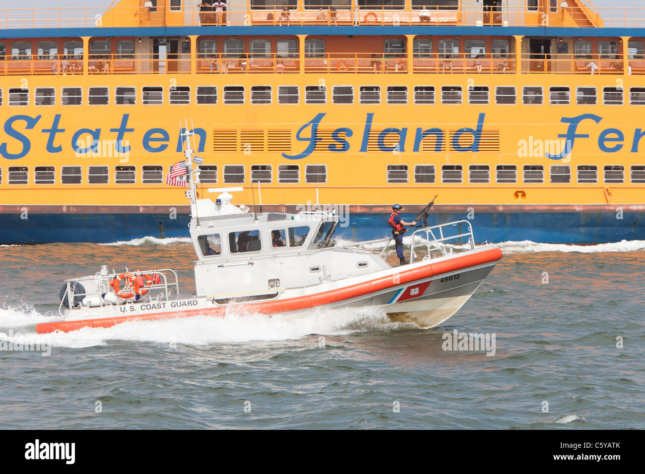 US Coast Guard Response Boat-Medium (RB-M) 45612 passes by the Staten Island Ferry on a mission in New York Harbor. - Stock Image