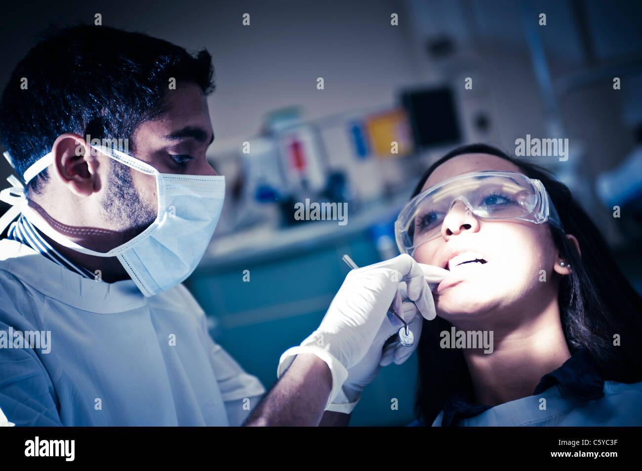 Male dentistry student performing dental surgery on female dentistry student in dentistry clinical setting - Stock Image