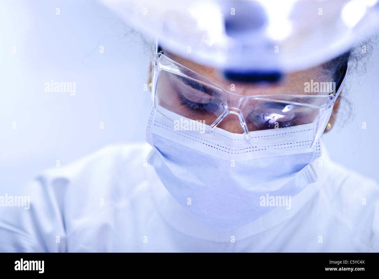 Close up of face of young female dentist wearing a surgical mask and goggles and white dental tunic looking down - Stock Image