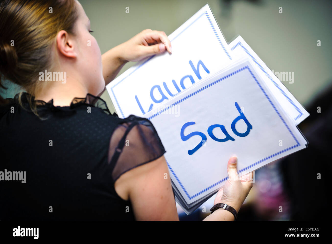 female caucasian teacher holding up cue cards saying laugh and sad - Stock Image