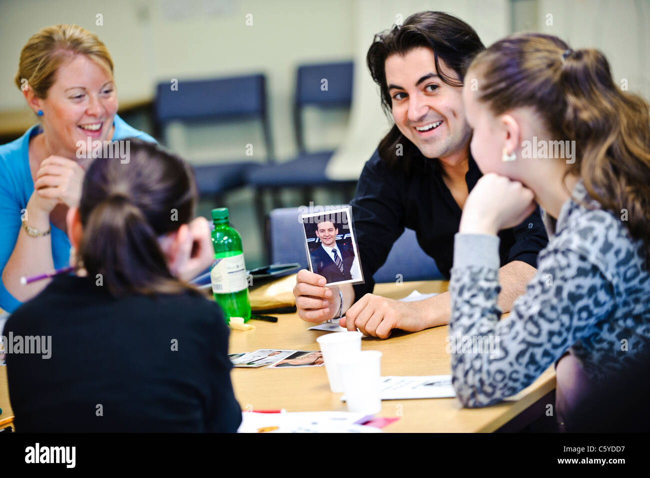 Adult teachers in classroom setting holding up a photo of a celebrity towards two school children aged 12 to 13 - Stock Image