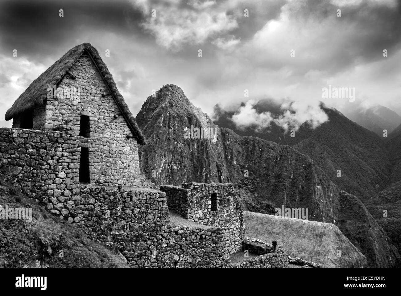 Scenic view of Machupicchu high up in the Peruvian Andes. With wooden hut and misty mountains. Monotone image. - Stock Image