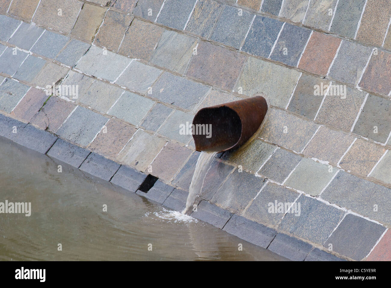Industrial waste water are discharged into a river withing the city boundaries. Water pollution issues - Stock Image