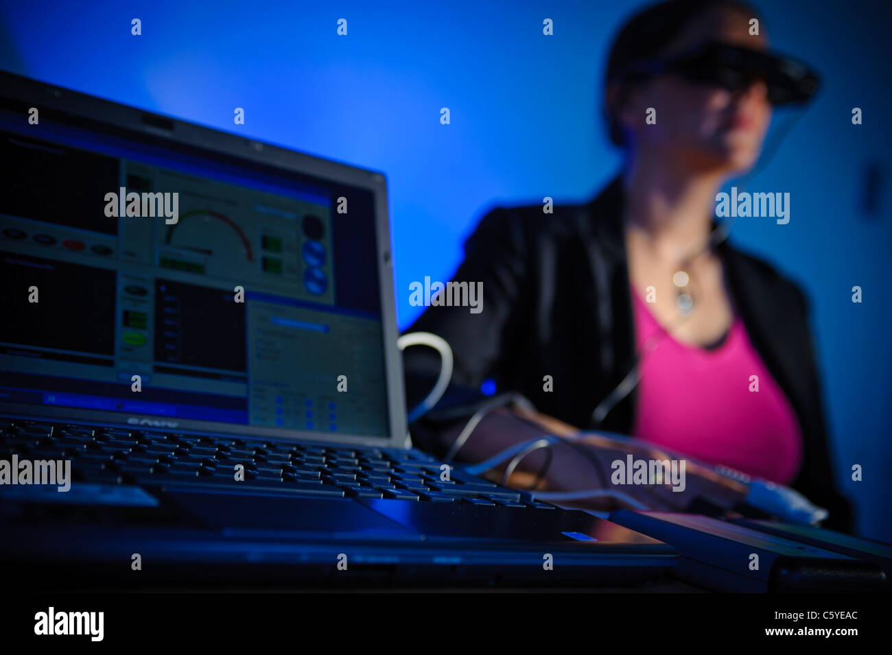 subject wearing virtual reality goggles in scientific study to treat phobia laptop showing results on screen in - Stock Image