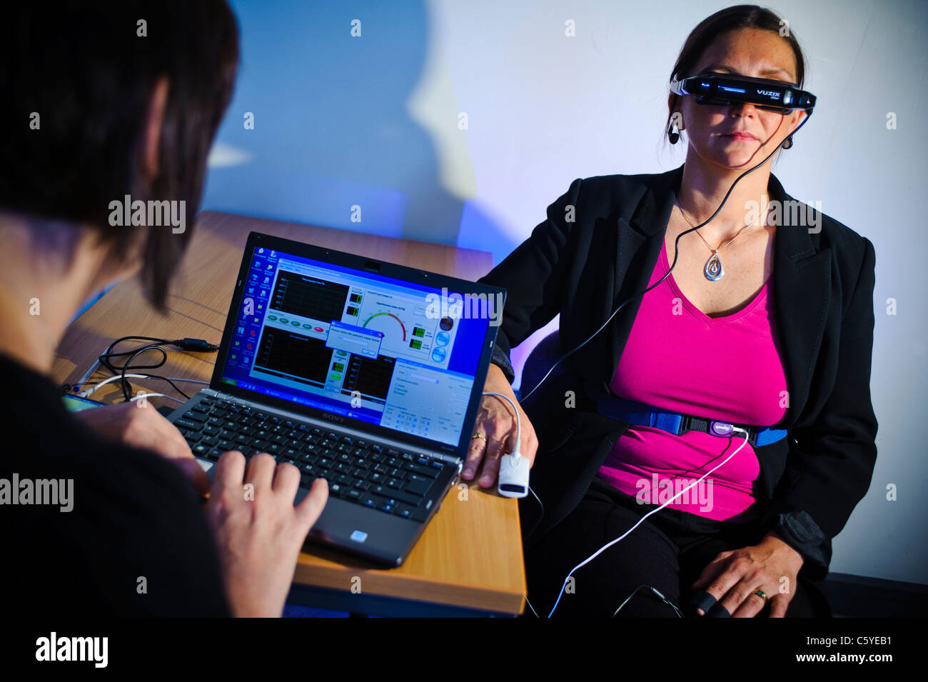 subject wearing virtual reality goggles in scientific study to treat phobia scientist monitoring results on laptop - Stock Image