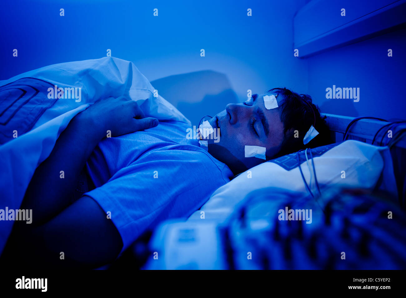 sleep lab EEG monitoring machine equipment and wires and electrodes with subject in background blue lighting - Stock Image