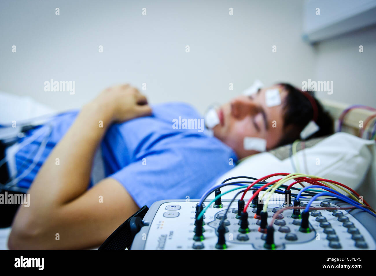 sleep lab EEG monitoring machine equipment electrodes and wires with subject in background blurred out - Stock Image