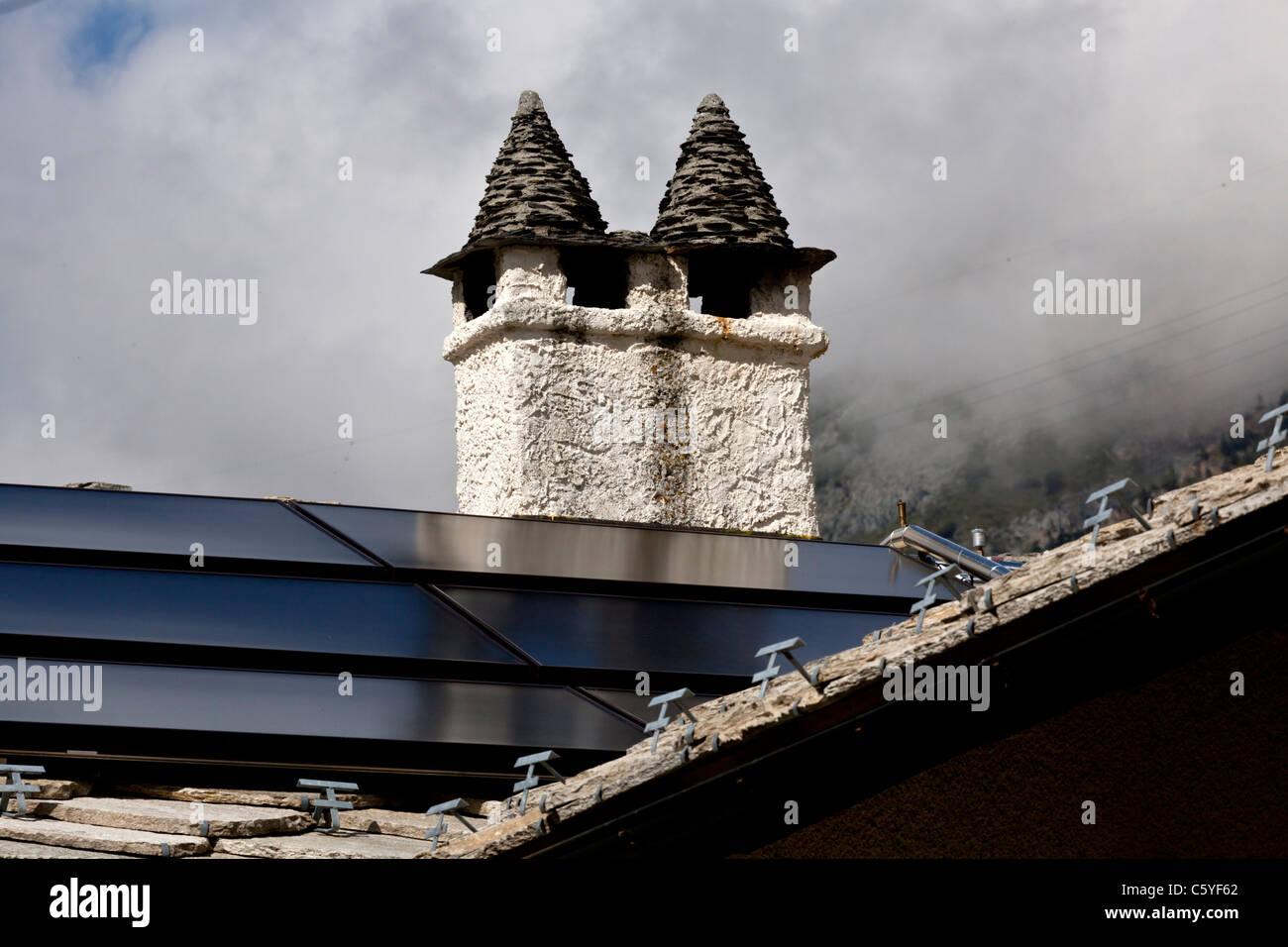 Chimney stacks on a roof covered with cut slates (Cogne - Italy). Souches de cheminées sur un toit de lauzes - Stock Image