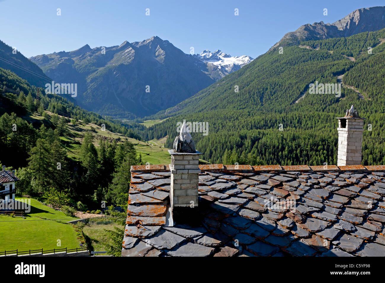 Chimney stacks on a roof covered with slates (Gimilan - Italy). Souches de cheminées sur un toit de lauzes - Stock Image