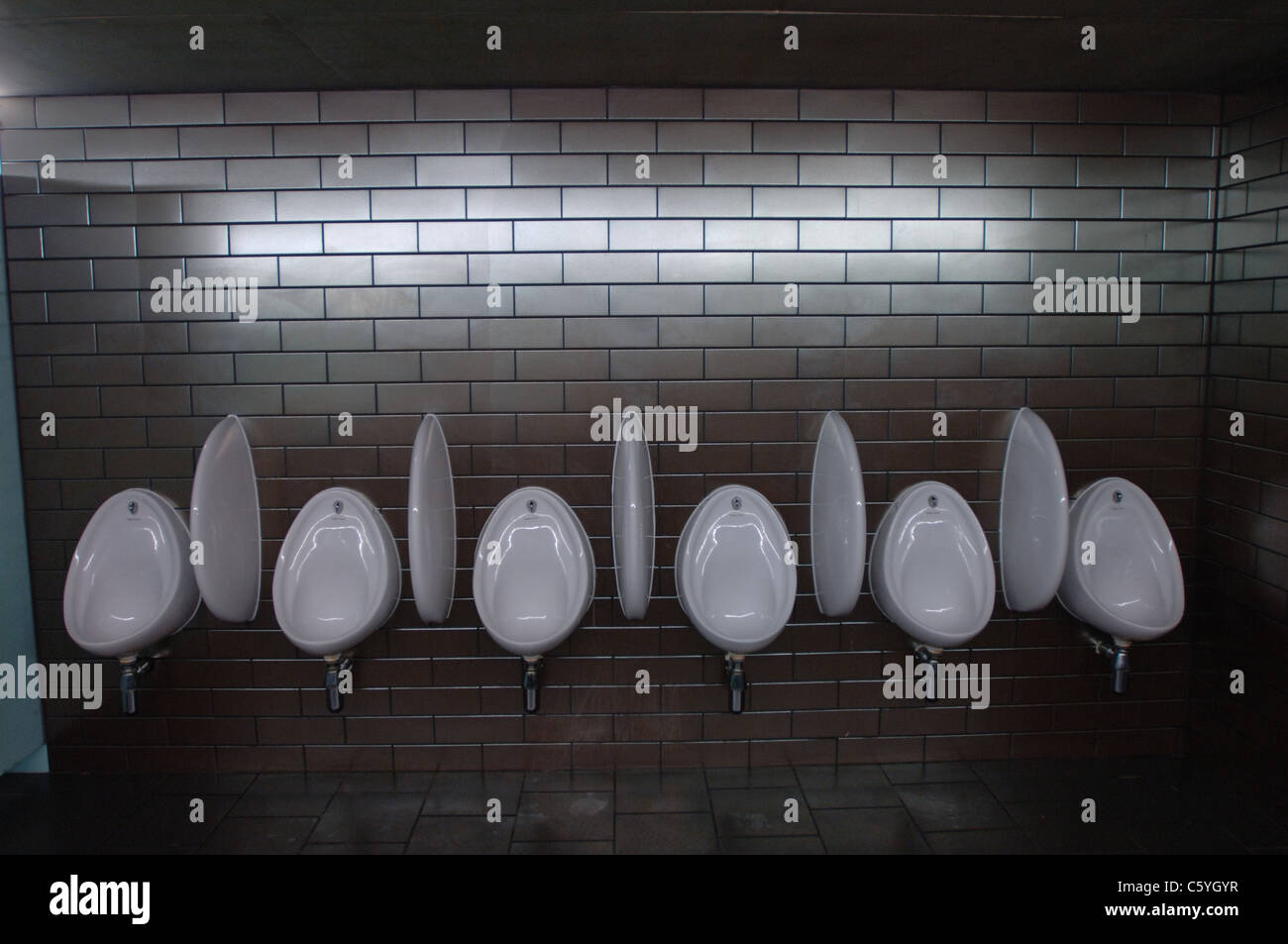 Row of six wall mounted urinals in a public toilet for men - Stock Image