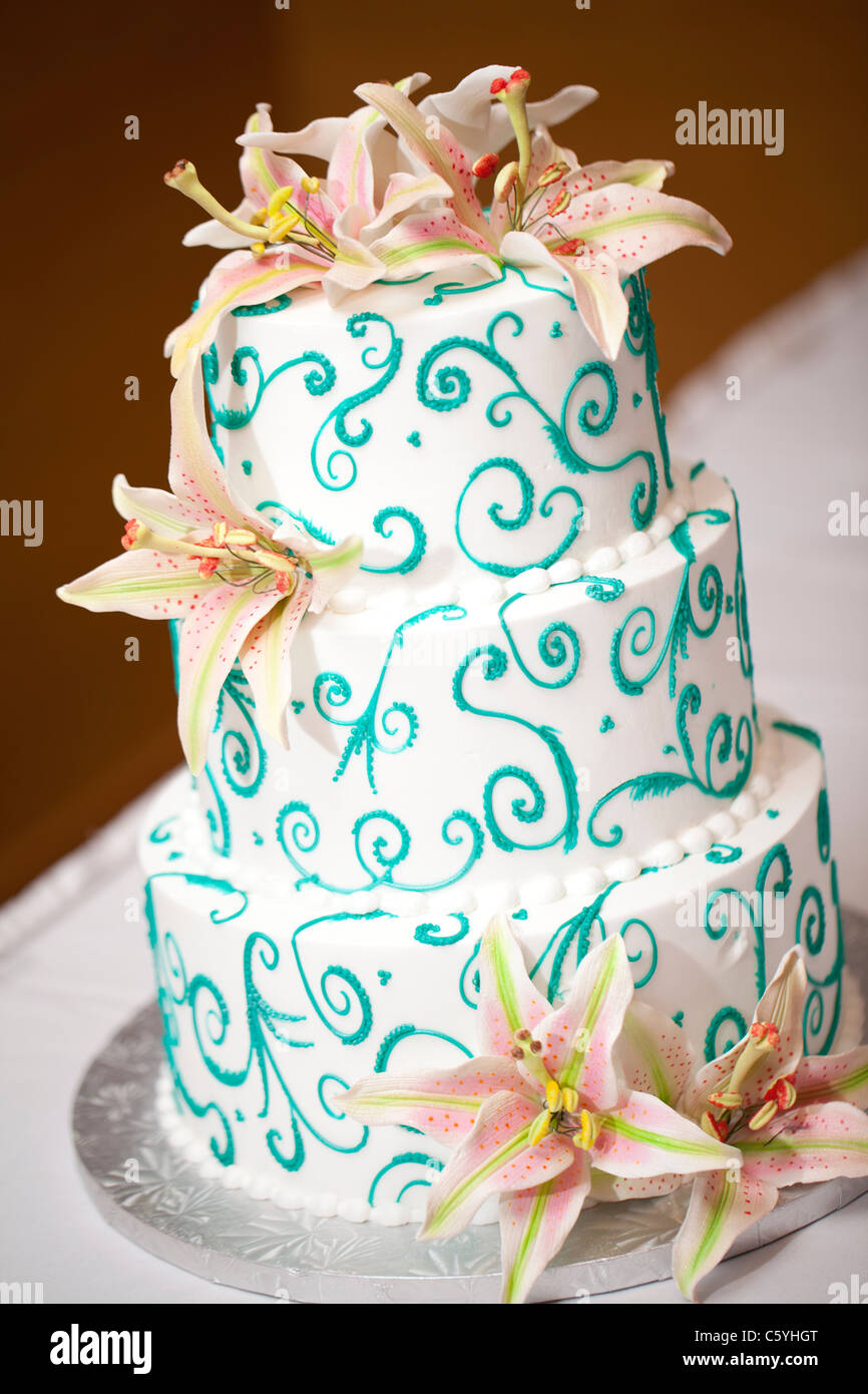 A three-tiered white and teal wedding cake covered with edible fondant lilies. - Stock Image