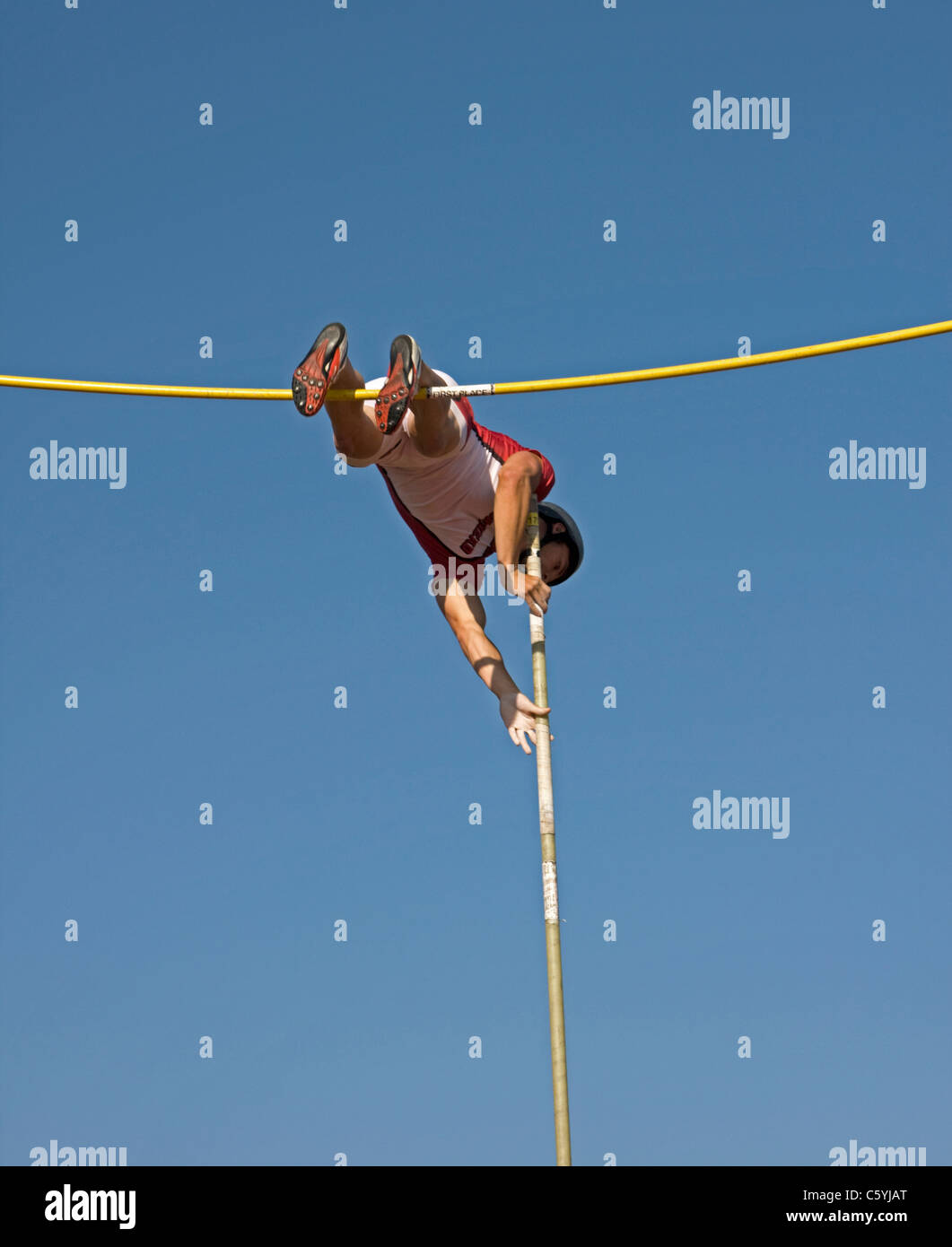 A high school boy makes a valiant attempt at clearing the pole vault bar at a sectional track meet in Wisconsin. - Stock Image