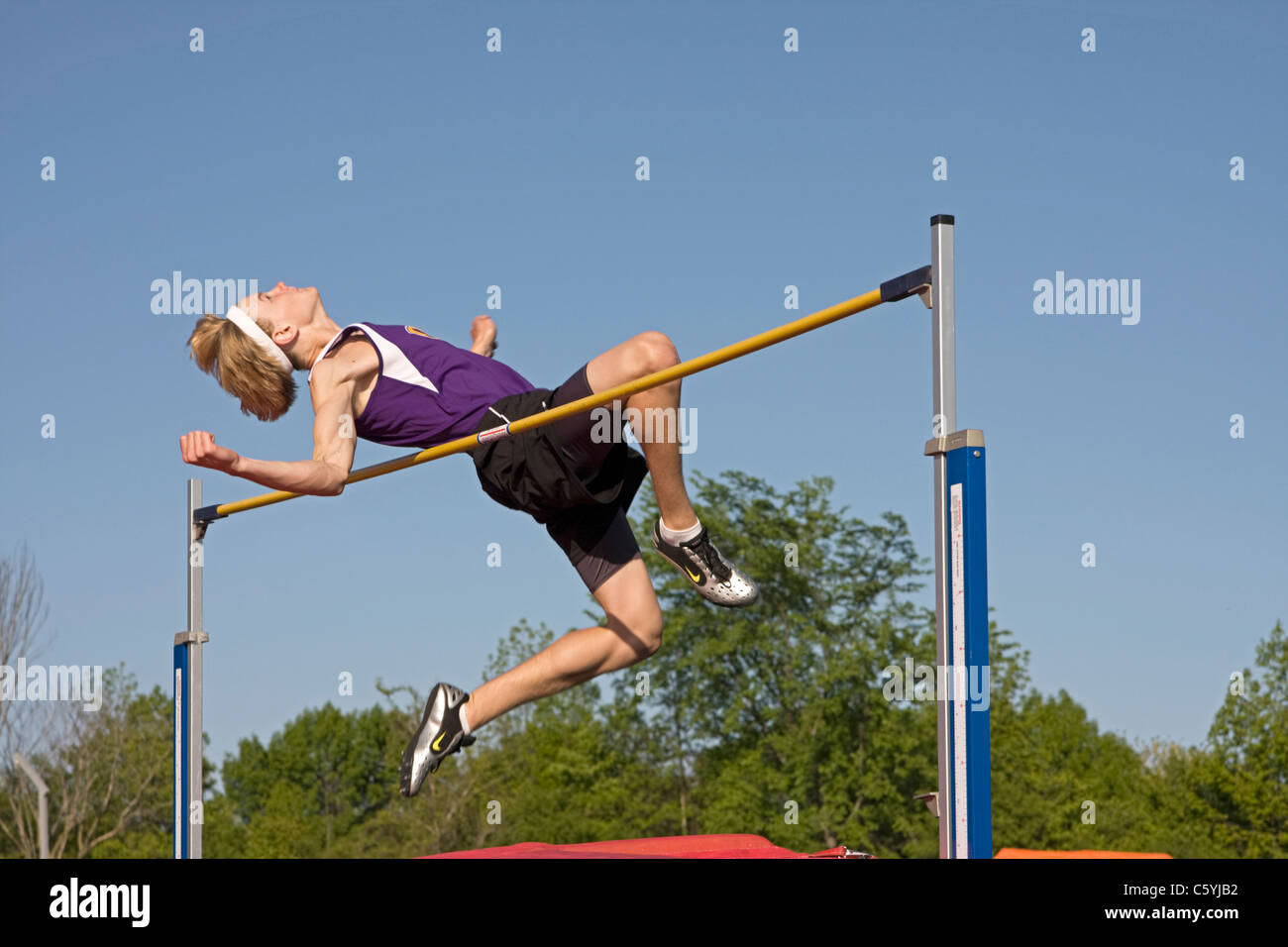 A high school boy uses his body language to wish himself over the high jump bar at a sectional track meet in Wisconsin. - Stock Image