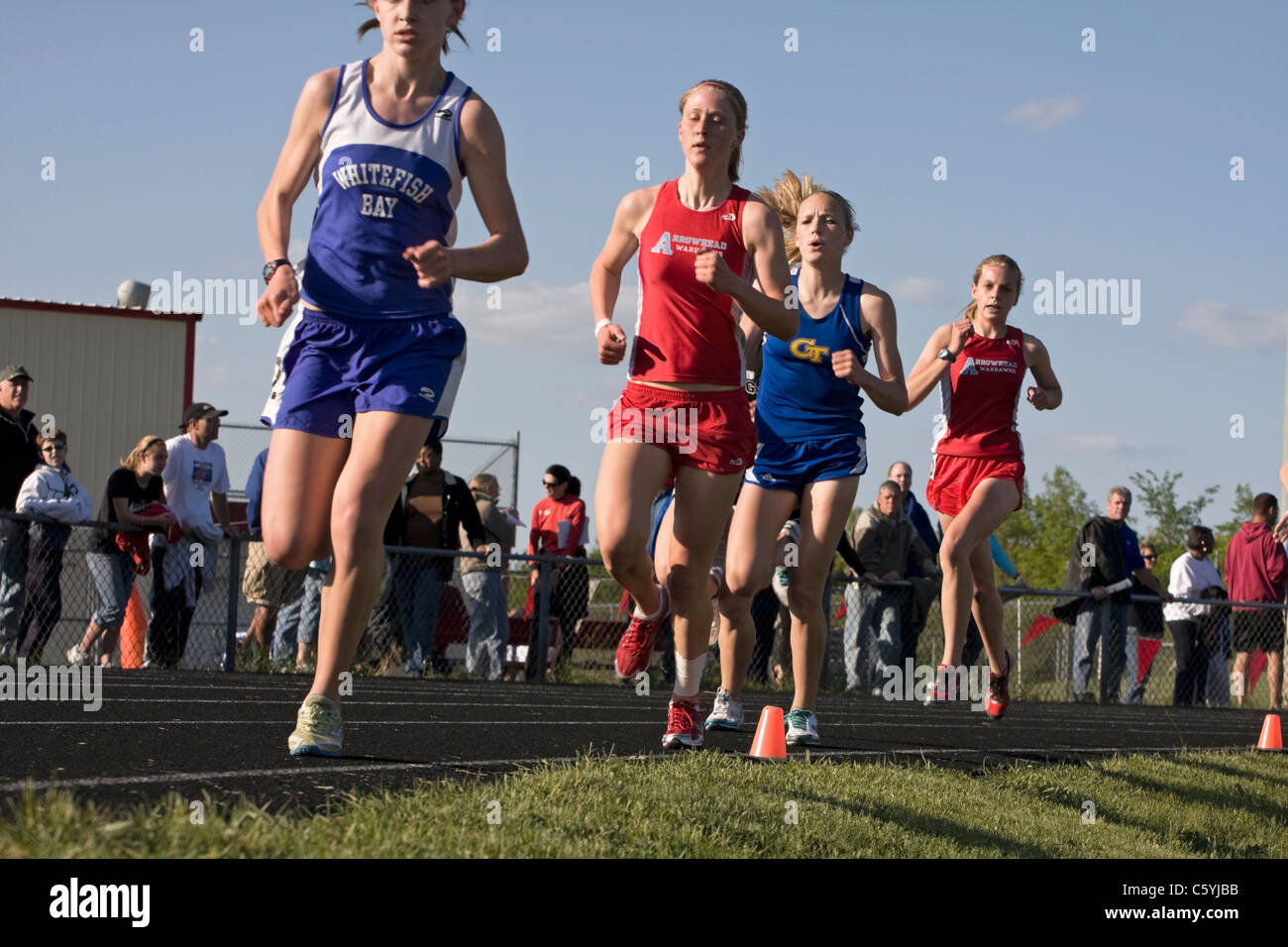High school girls round the last turn at a sectional track meet in Wisconsin. - Stock Image