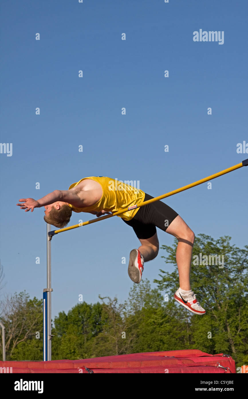 A high school boy tries to clear the high jump bar at a sectional track meet in Wisconsin. - Stock Image