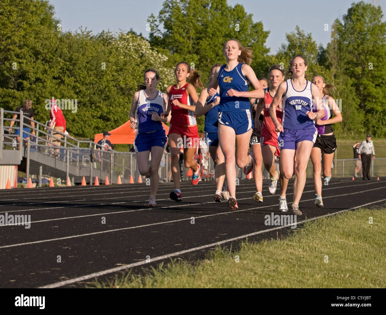 High school girls run in a pack at the sectional track meet in Wisconsin. - Stock Image