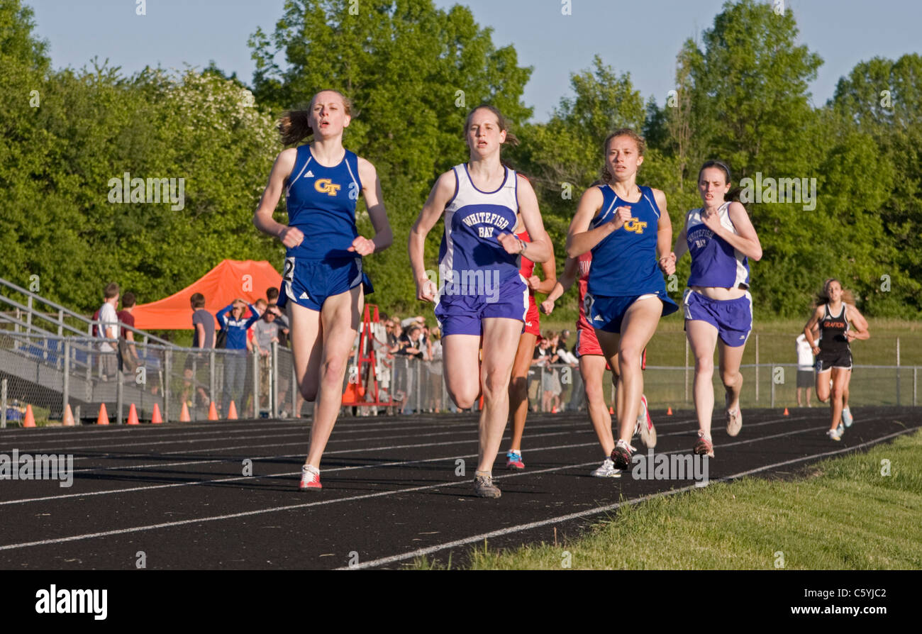 High school girls run elbow to elbow at the sectional track meet in Wisconsin. - Stock Image