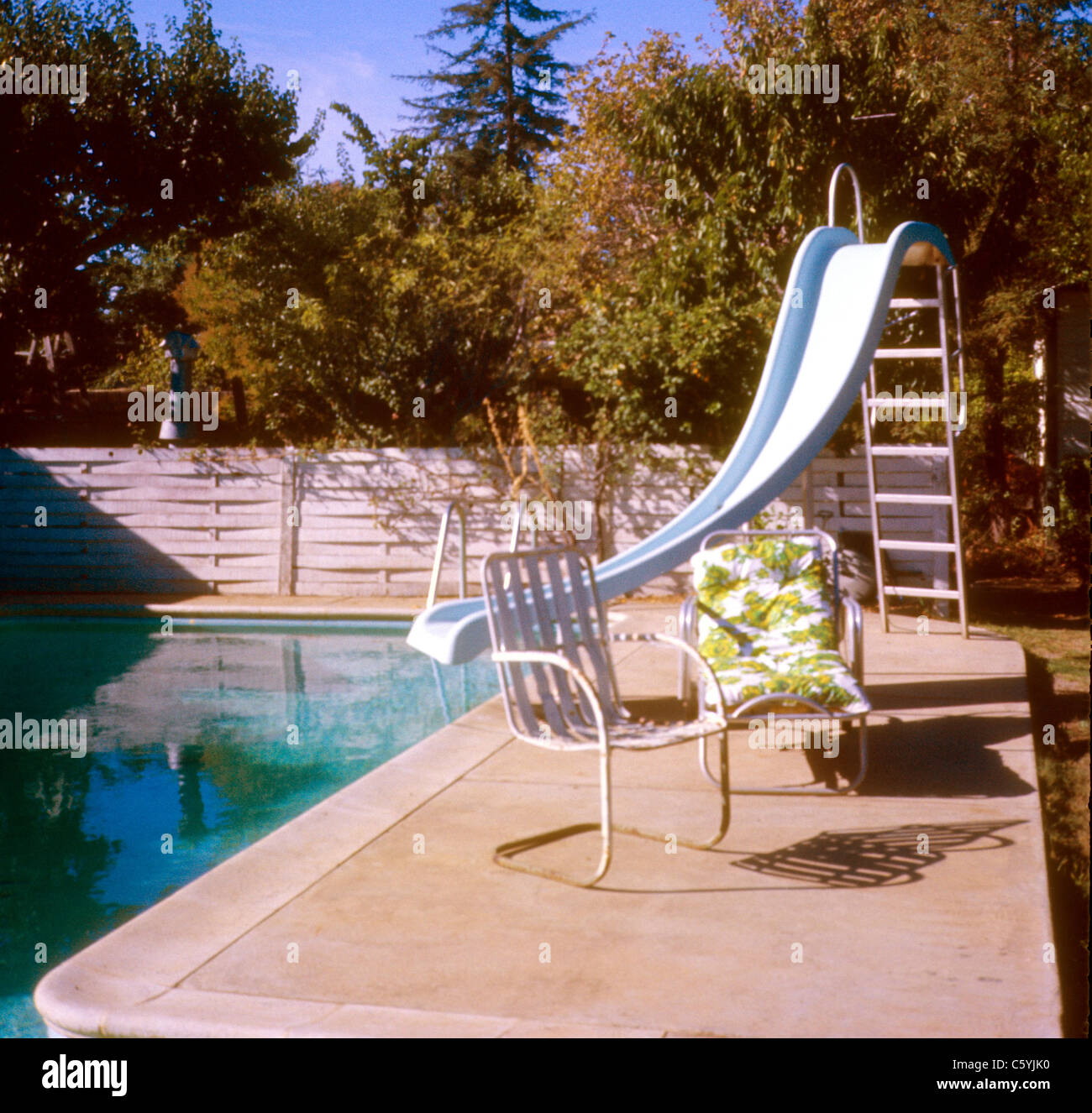 backyard dug in swimming pool with slide and 70s chair 1977 1970s architecture decor furniture lawn - Stock Image