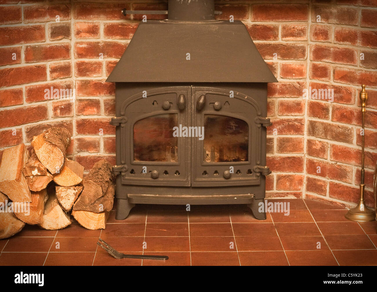 A wood burning stove in a red brick fireplace - Stock Image