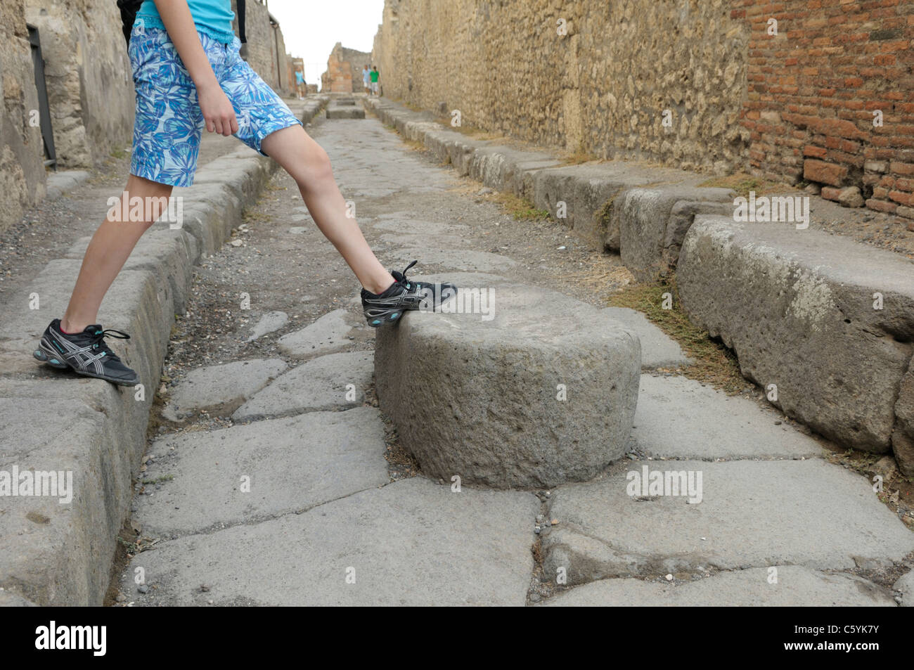 Crossing a street at Pompeii.  The large stones helped citizens cross sloppy roads while also allowing mule carts - Stock Image