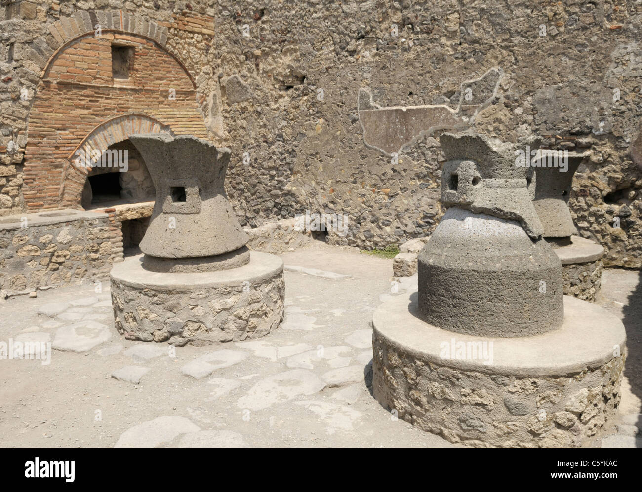 Bakery, Pompeii. In  foreground are millstones that were turned by mules. In back is the wood burning oven. - Stock Image