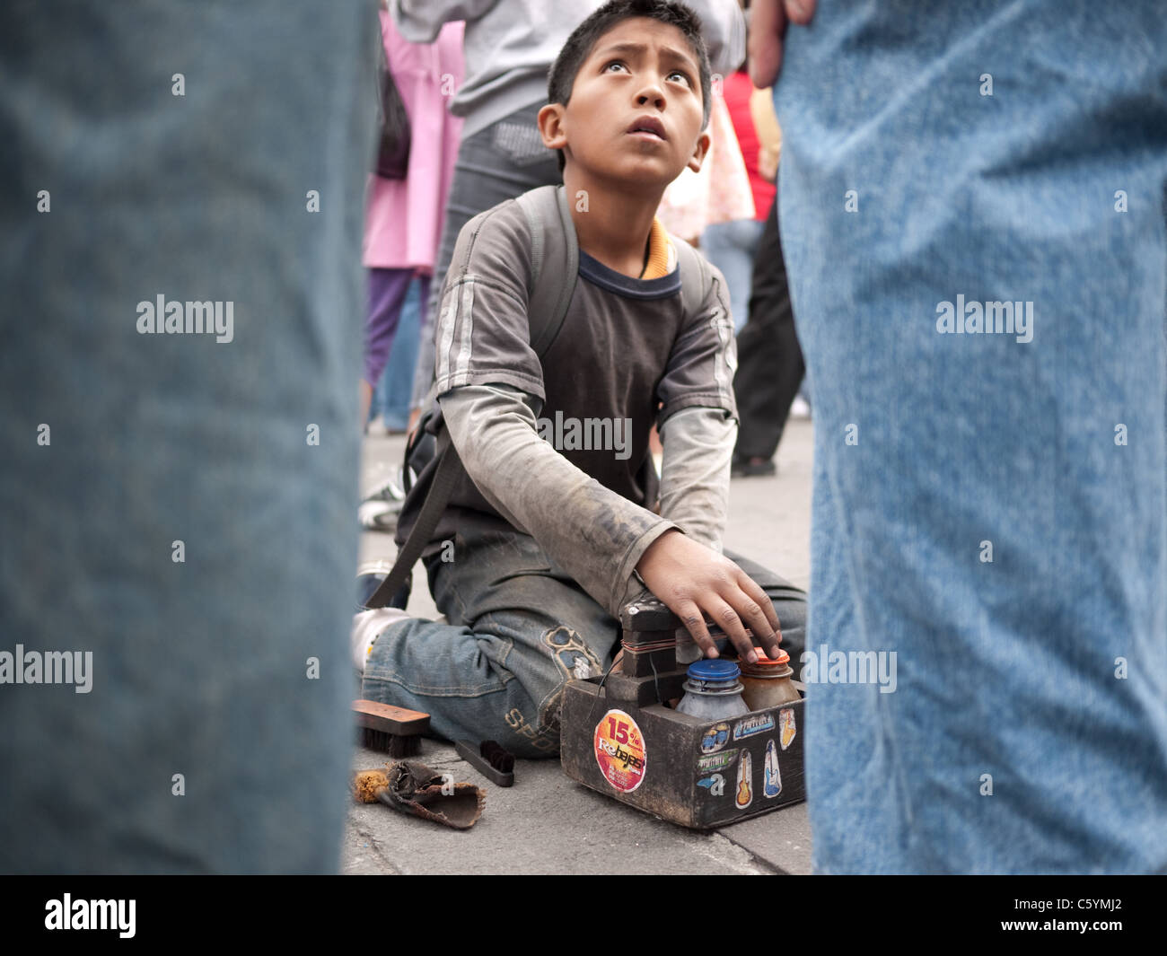 A young shoe shiner looks up at a client while polishing his shoes. - Stock Image