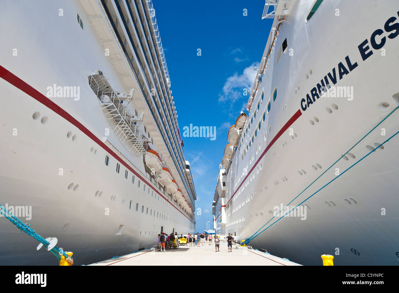 Cruise ship passengers on pier near Carnival cruise ships Triumph and Ecstasy in Cozumel, Mexico in the Caribbean - Stock Image