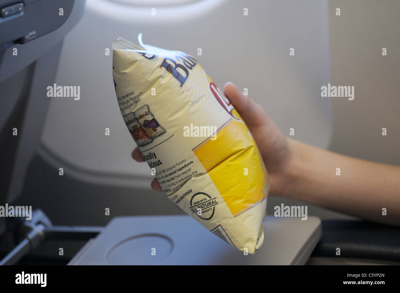 Chip bag puffed up because of lower atmospheric pressure at high altitude (38,000 feet on airline). Sequence with - Stock Image