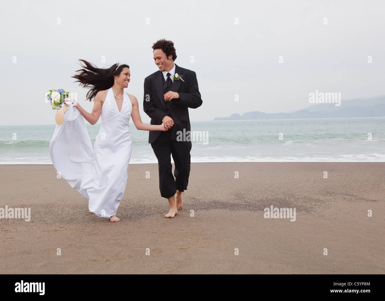 USA, California, San Francisco, Baker Beach, bride and groom walking on beach - Stock Image