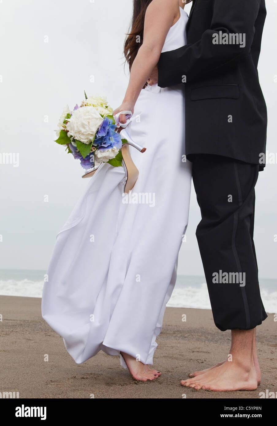 USA, California, San Francisco, Baker Beach, bride and groom walking on beach Stock Photo