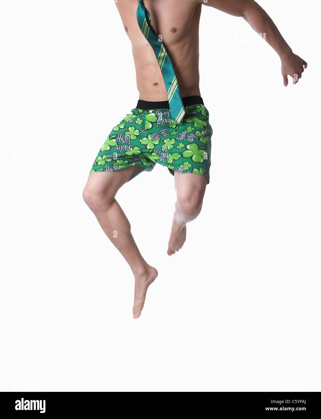 USA California, Fairfax, studio shot of young man wearing green boxer shorts with shamrocks jumping , low section - Stock Image