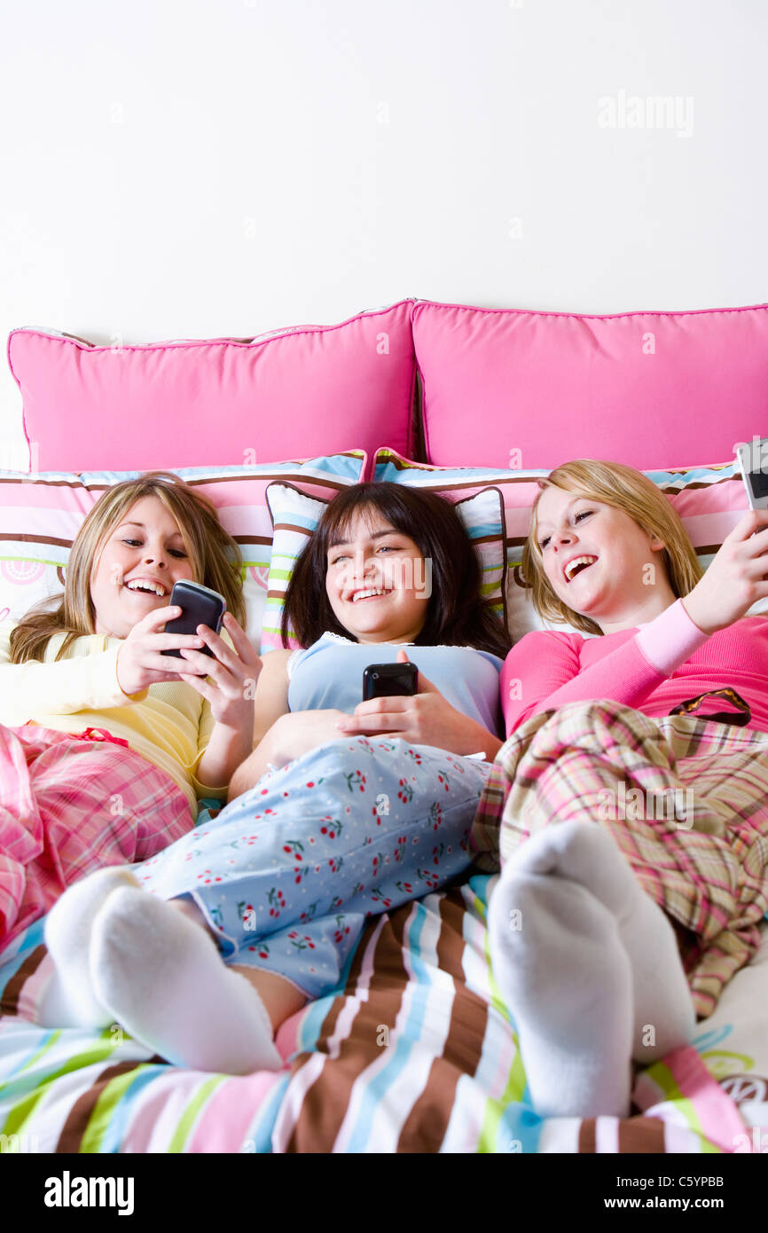 USA California, Fairfax, teenage girls (14-15, 16-17) lying on bed and looking at mobile phones - Stock Image
