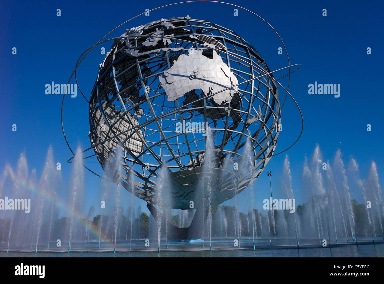 sun sets on the Unisphere World's fair US Steel NY New York Big Apple tourism bygone era fountain water jets - Stock Image