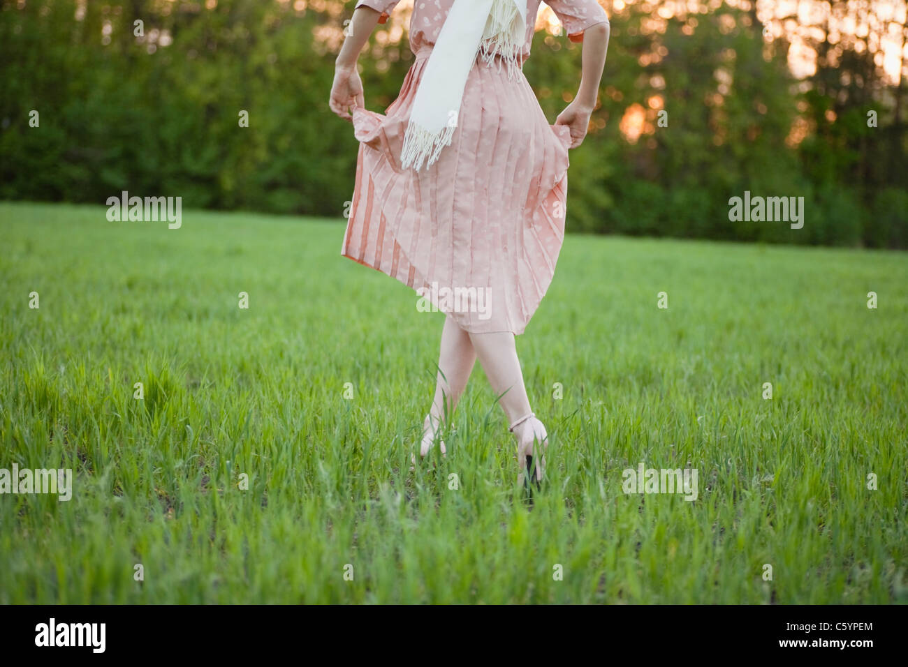 Russia, Voronezh, woman in dress running across meadow - Stock Image