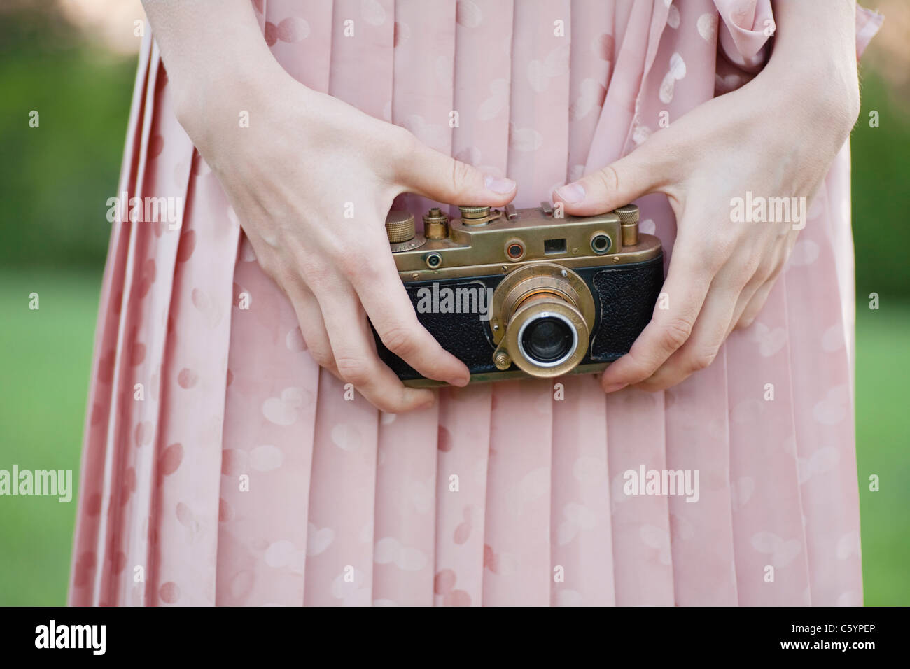 Russia, Voronezh, midsection of woman holding old camera - Stock Image