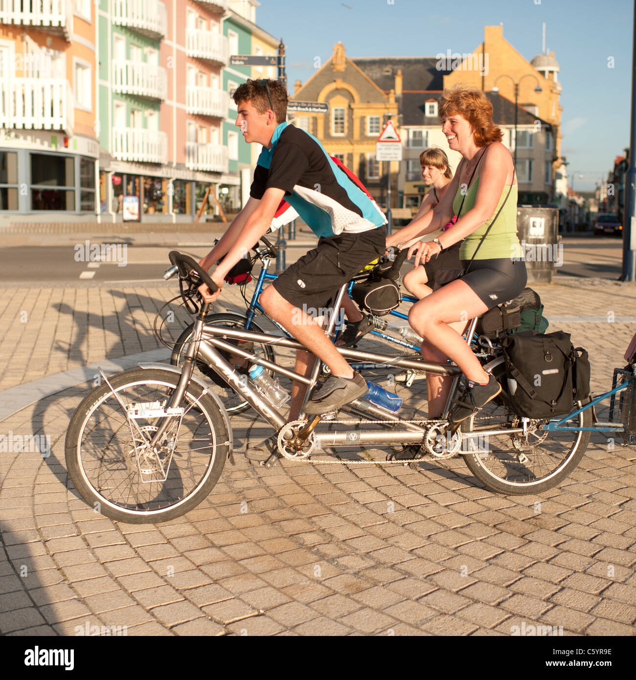 a family riding a pair of tandems on a cycling holiday , Aberystwyth Wales UK - Stock Image