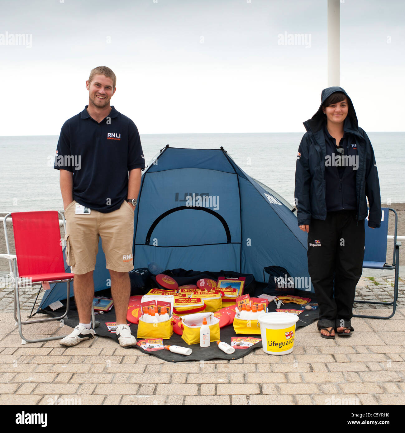 two RNLI workers selling branded items to raise money for the charity, Aberystwyth Wales UK - Stock Image