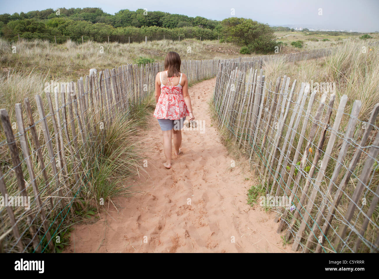 A woman walks down a sand track toward the sea front and beach - Stock Image