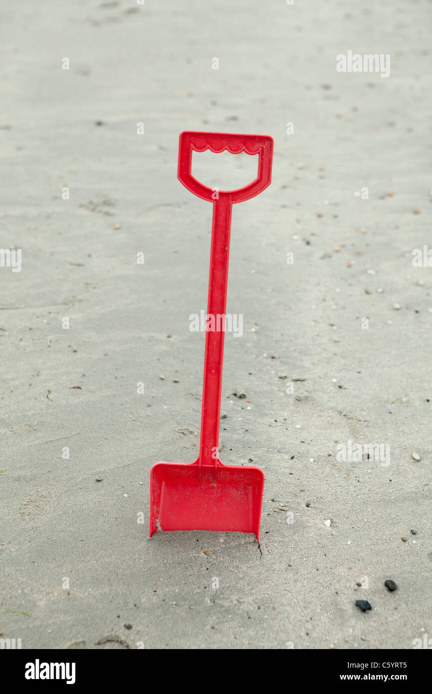 Red plastic spade on a beach - Stock Image