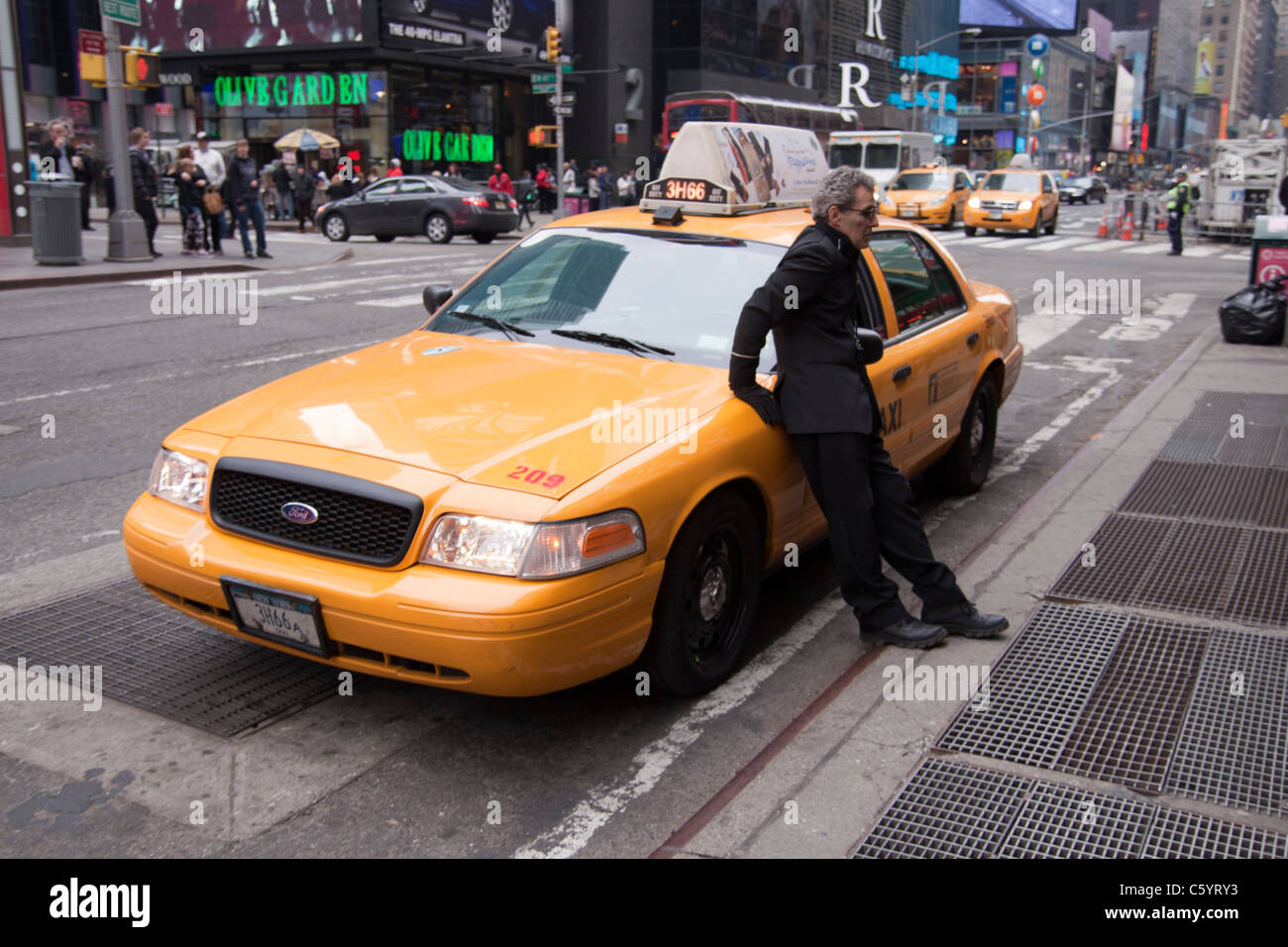 A driver leaning on his Yellow cab in Times Square New York. - Stock Image