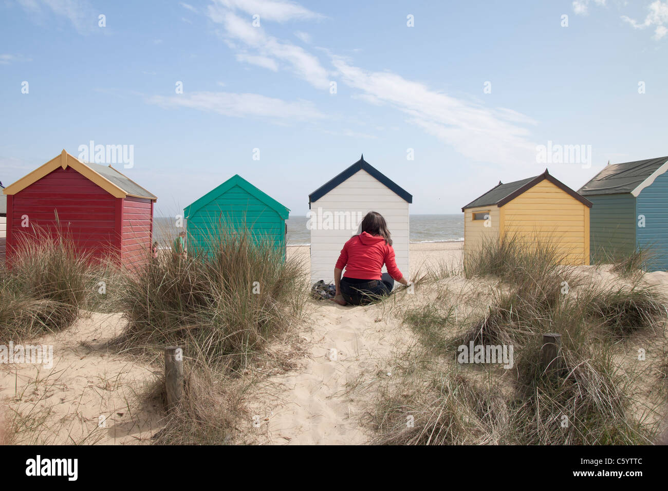 A girl sitting in front of the Beach Huts of Southwold beach in Suffolk, England. - Stock Image