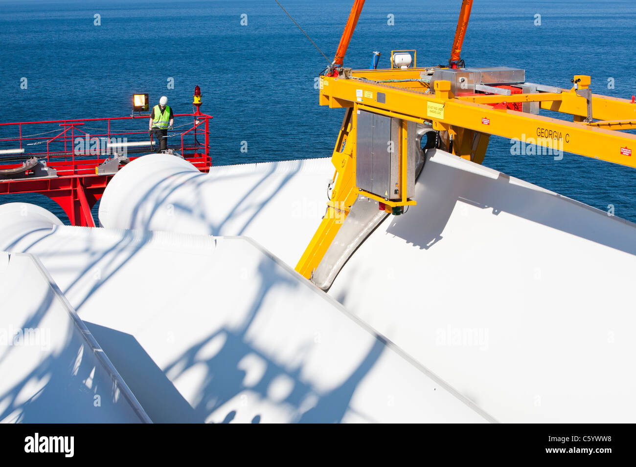 Workers prepare to lift a turbine blade for construction of the Walney offshore wind farm - Stock Image