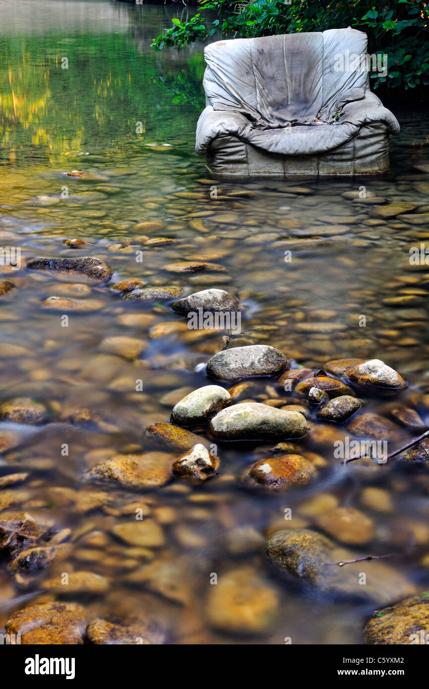 Fly tipping. An old armchair illegally dumped in a clear woodland stream. - Stock Image