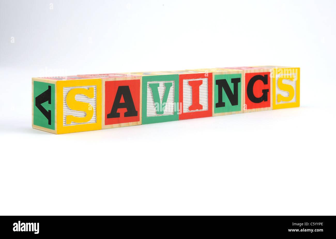 the word 'savings' spelled with children's letter blocks - Stock Image