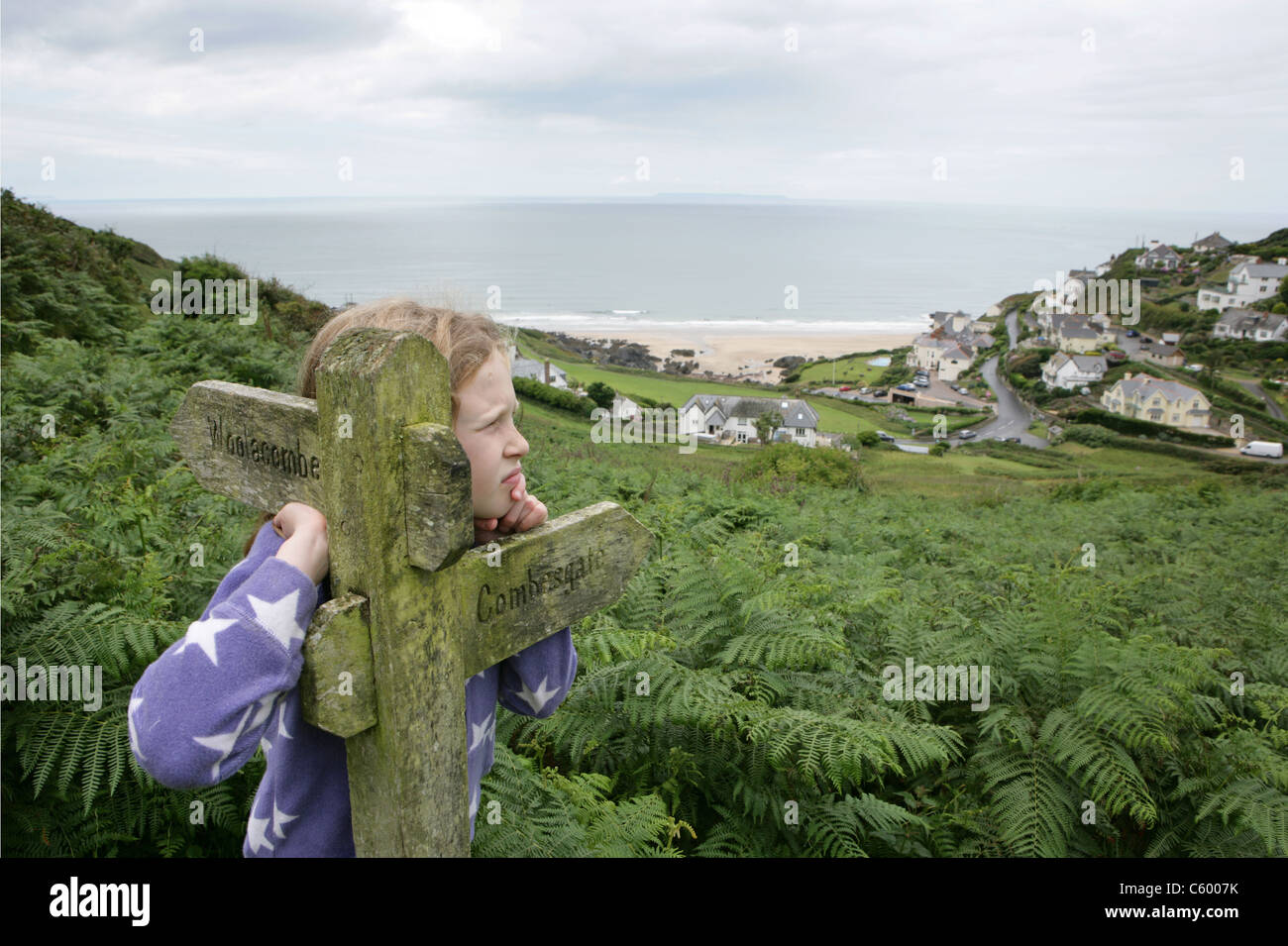 A young girl  beside a direction sign on the coastal path above Mortehoe Beach, Woolacombe in North Devon - Stock Image